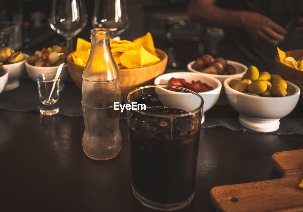 food and drink, table, glass, food, drinking glass, freshness, household equipment, indoors, drink, real people, refreshment, incidental people, human hand, bowl, one person, focus on foreground, hand, preparation, healthy eating, glass - material