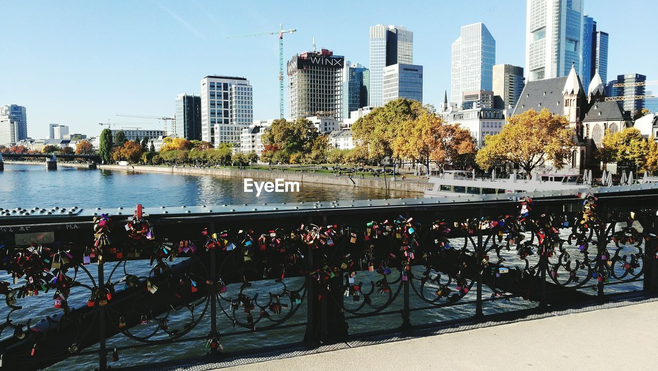 architecture, city, railing, built structure, skyscraper, building exterior, river, bridge - man made structure, outdoors, day, love lock, cityscape, tree, city life, urban skyline, water, clear sky, sky, no people