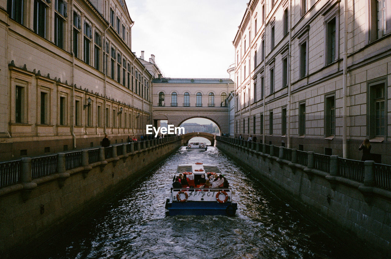 People In Canal In City Against Sky