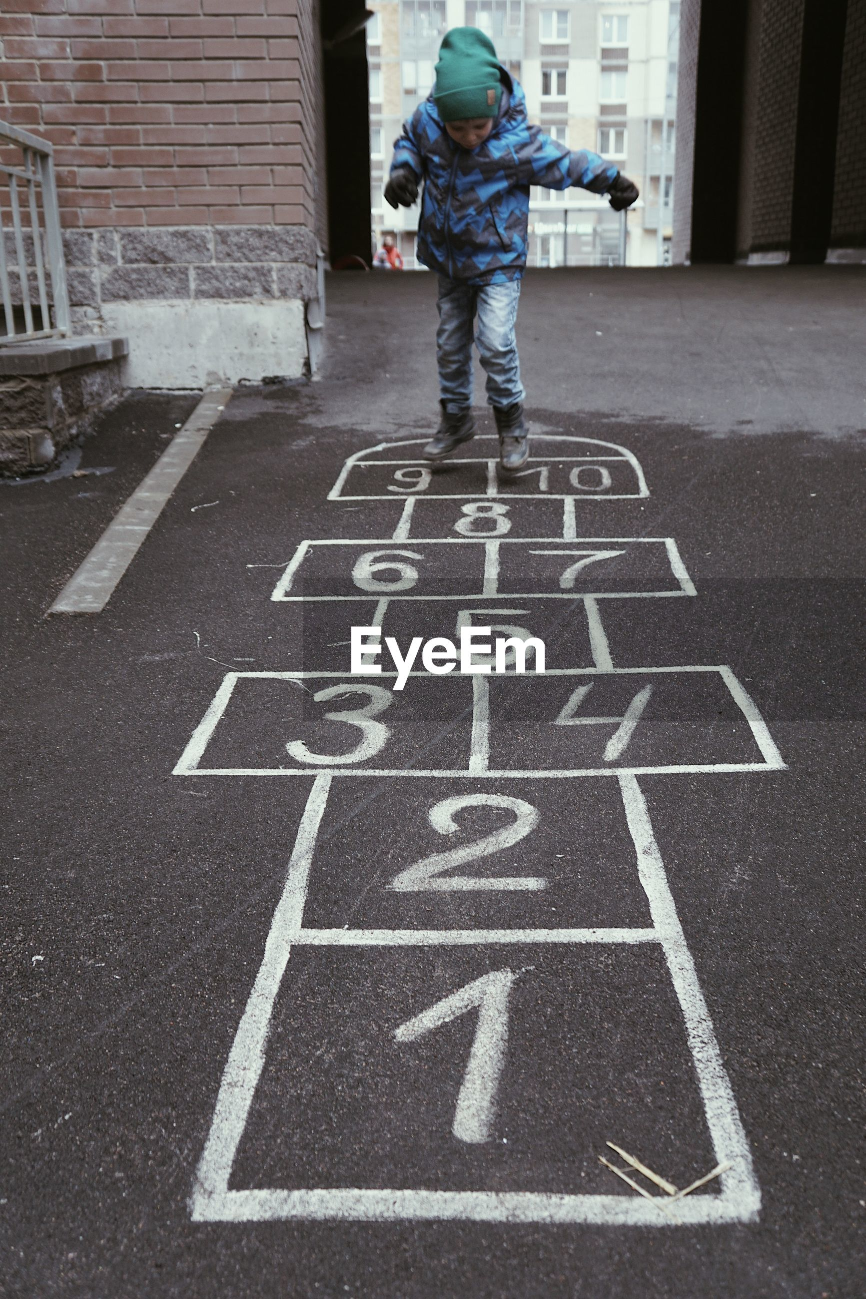 Boy playing hopscotch on street