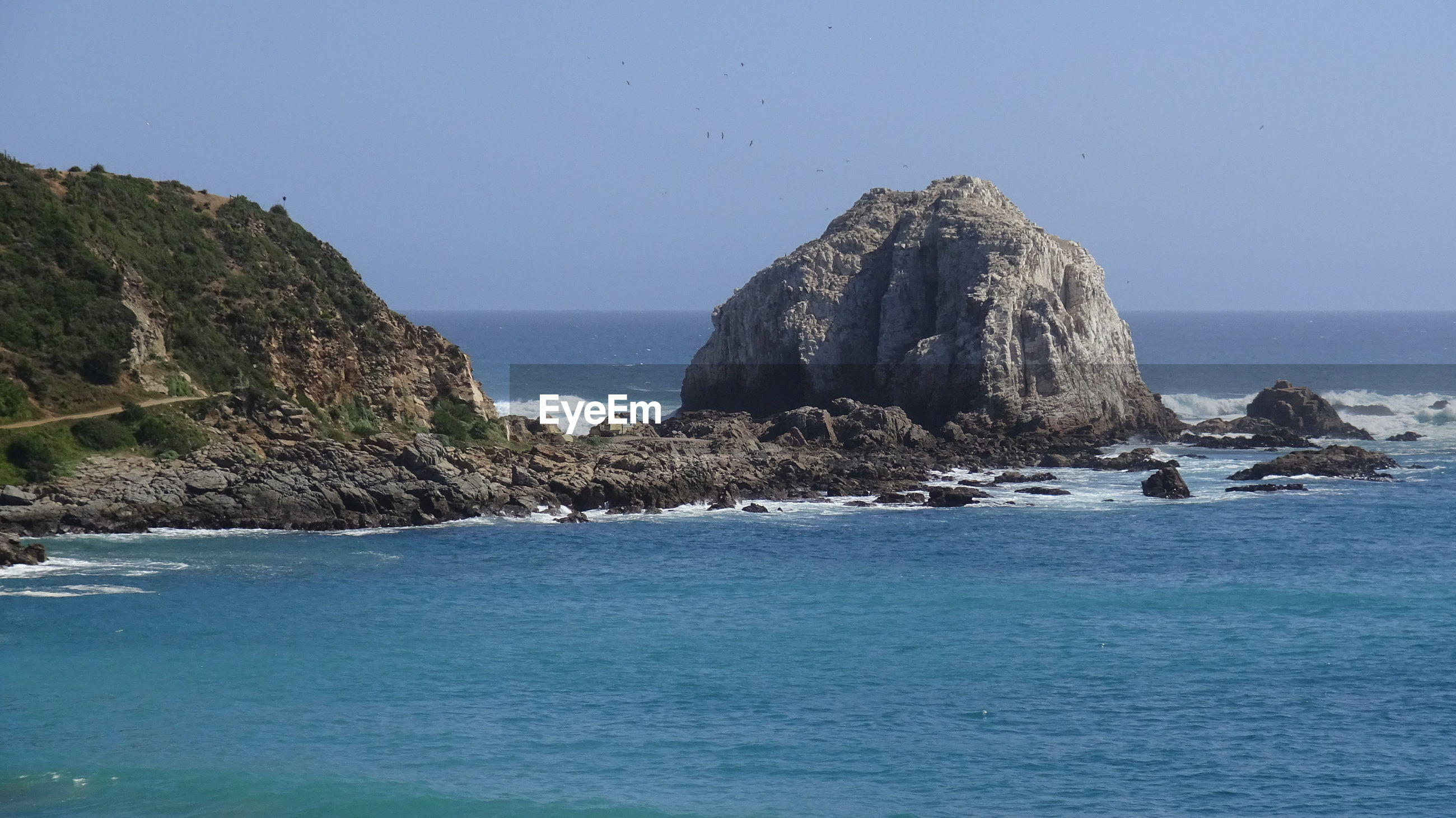 ROCK FORMATIONS IN SEA AGAINST CLEAR BLUE SKY