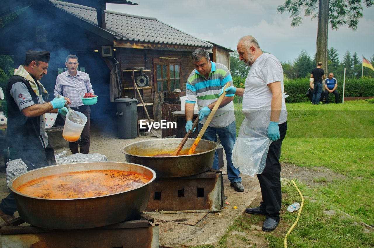 men, group of people, real people, preparation, food, adult, males, day, people, casual clothing, food and drink, full length, preparing food, mature adult, kitchen utensil, women, lifestyles, standing, occupation, mature men, outdoors