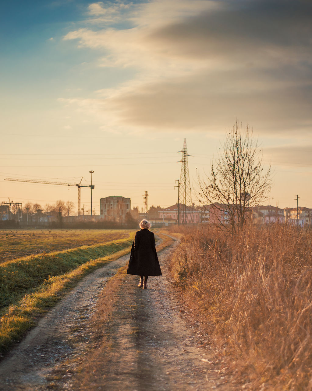 Rear View Of Woman Walking On Road Against Sky During Sunset