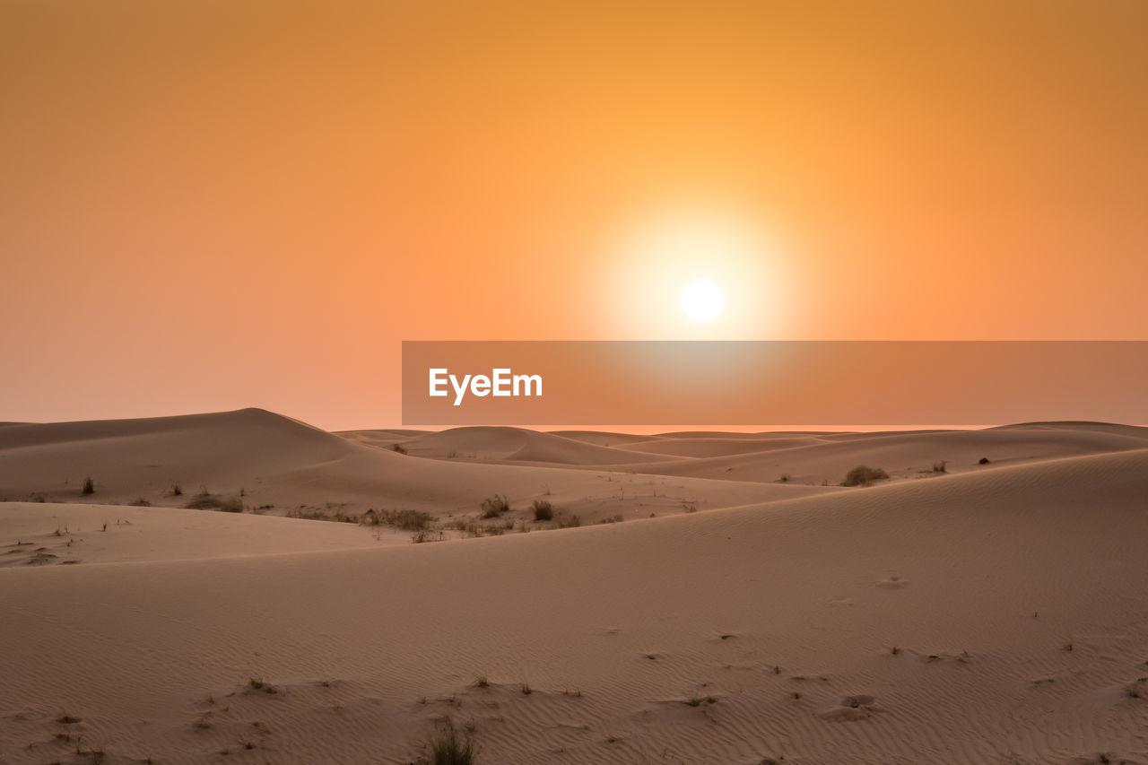 SCENIC VIEW OF DESERT AGAINST SUNSET SKY