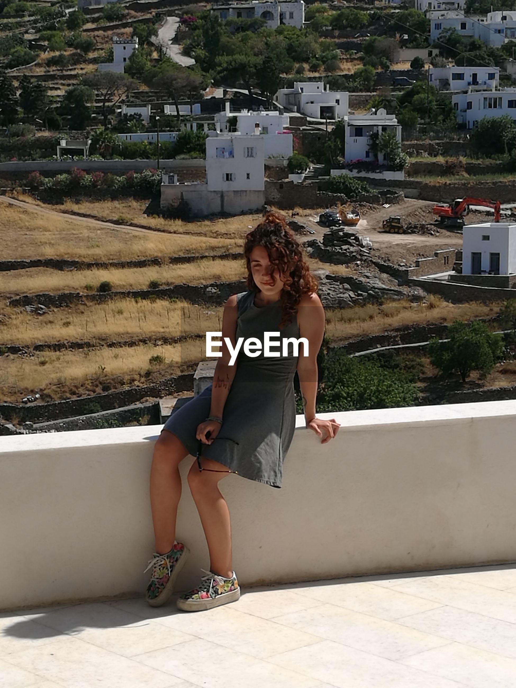 Full length of teenage girl sitting on railing against buildings