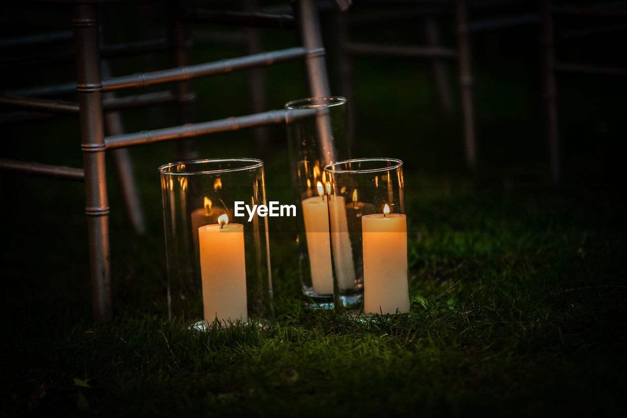 burning, fire, candle, flame, fire - natural phenomenon, illuminated, no people, heat - temperature, glowing, nature, close-up, selective focus, grass, lighting equipment, glass - material, land, container, transparent, night, plant, dark, glass