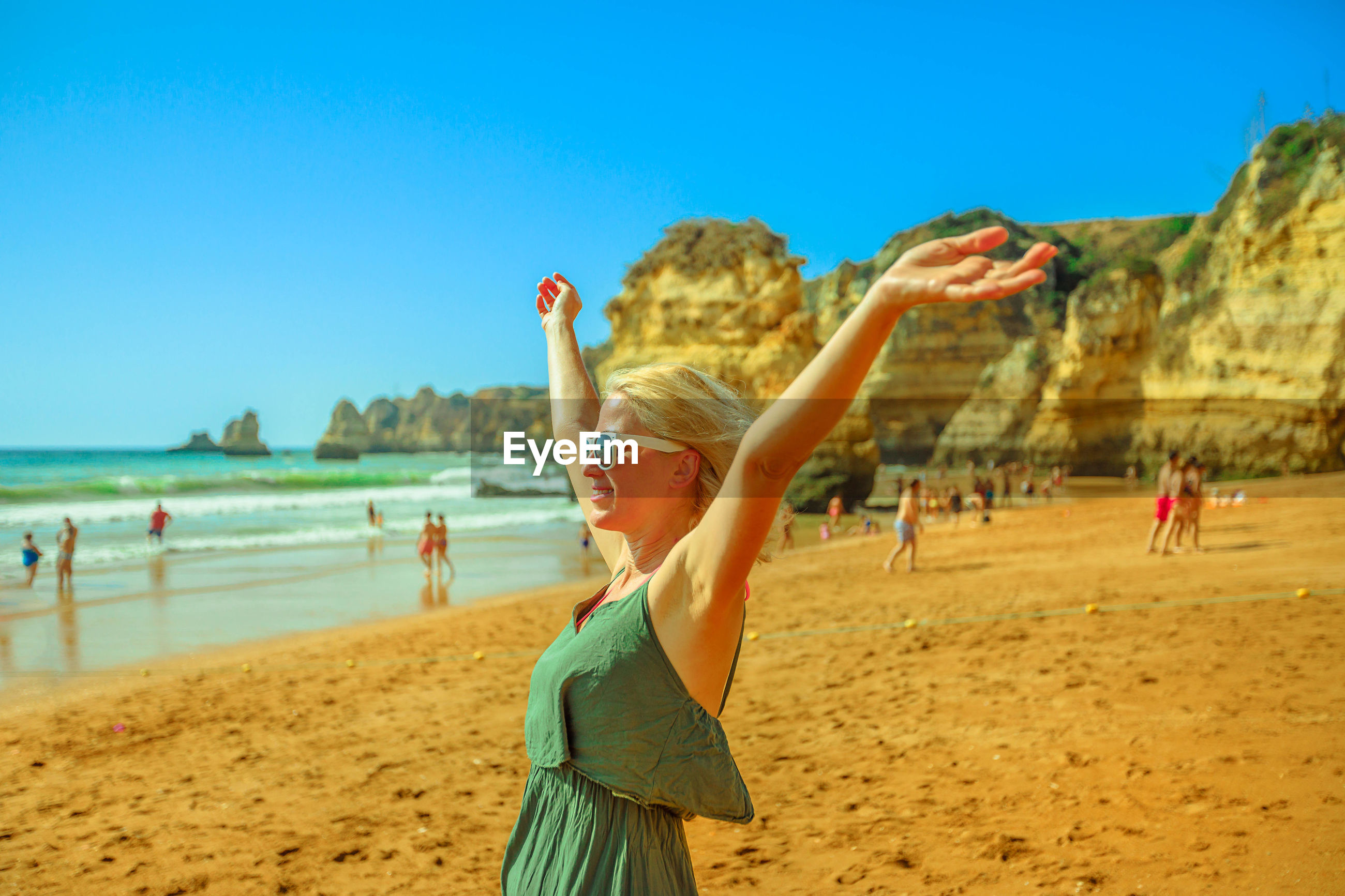 Woman with arms outstretched standing at beach