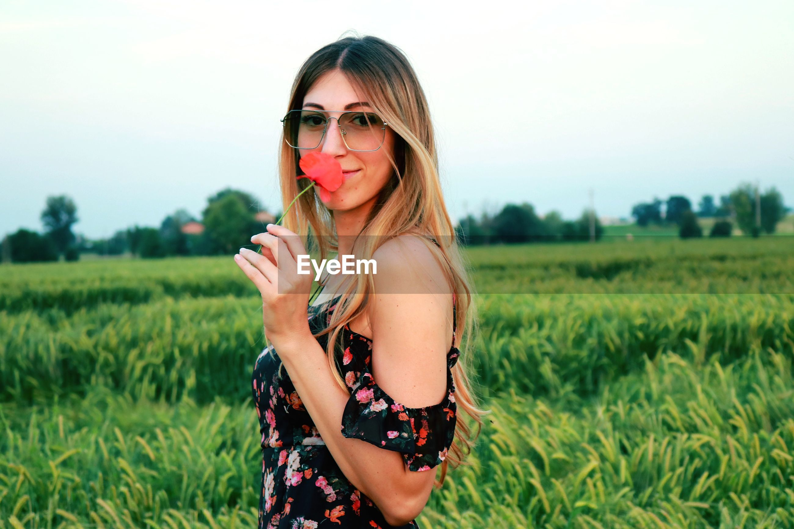 Portrait of young woman holding flower while standing on field