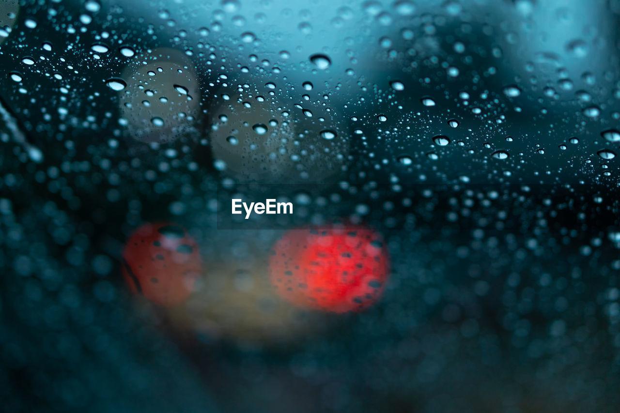 Close-Up Of Wet Glass Window During Rainy Season