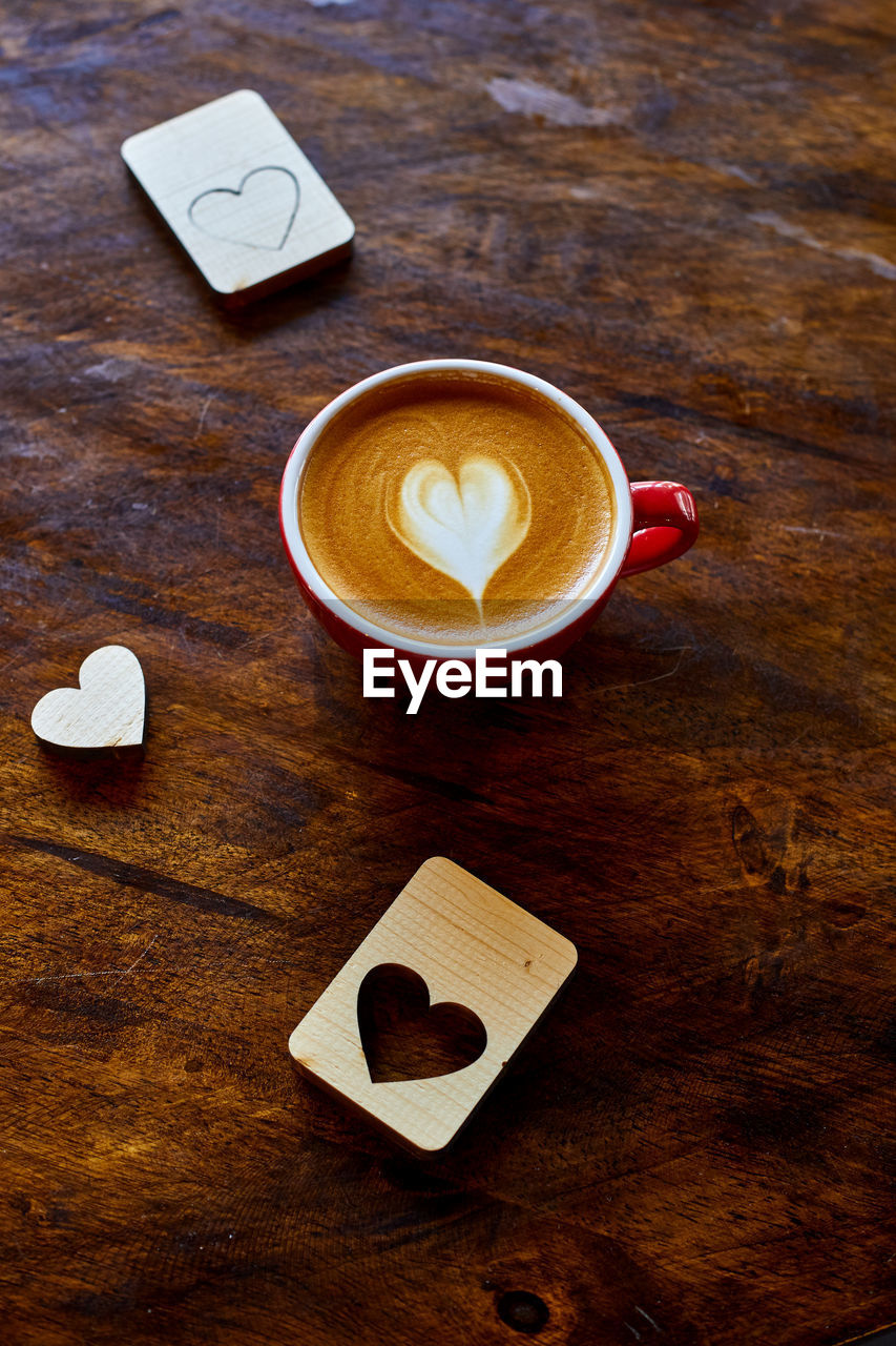 coffee, coffee - drink, drink, refreshment, cup, coffee cup, food and drink, mug, wood - material, table, still life, frothy drink, hot drink, heart shape, indoors, froth art, no people, high angle view, cappuccino, love, crockery, latte, non-alcoholic beverage