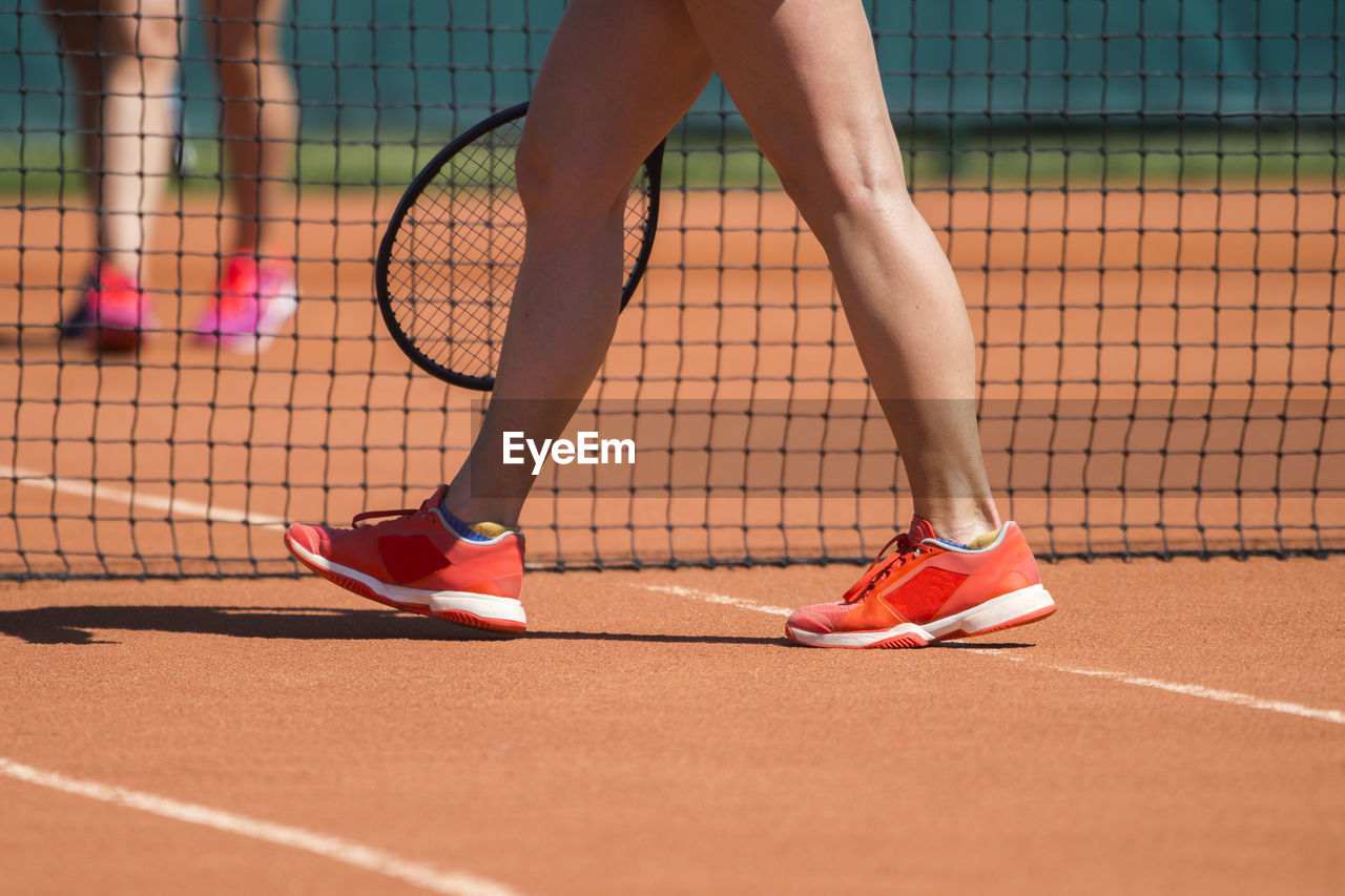 Low section of woman walking on tennis court