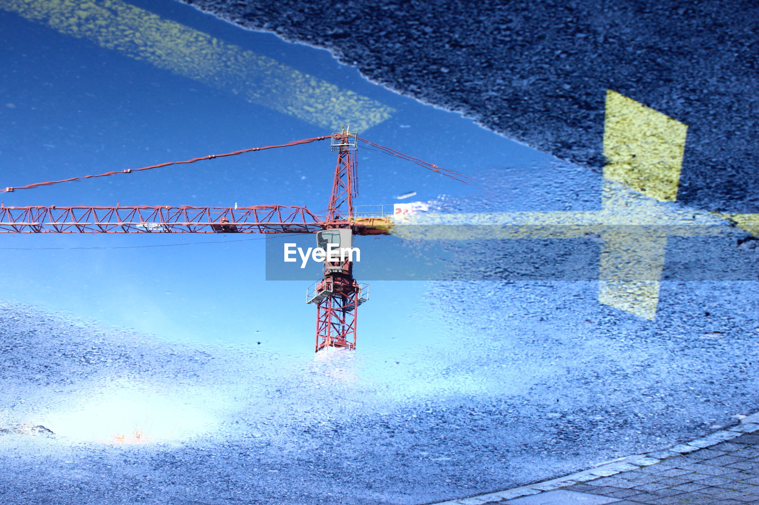 Reflection of crane in puddle