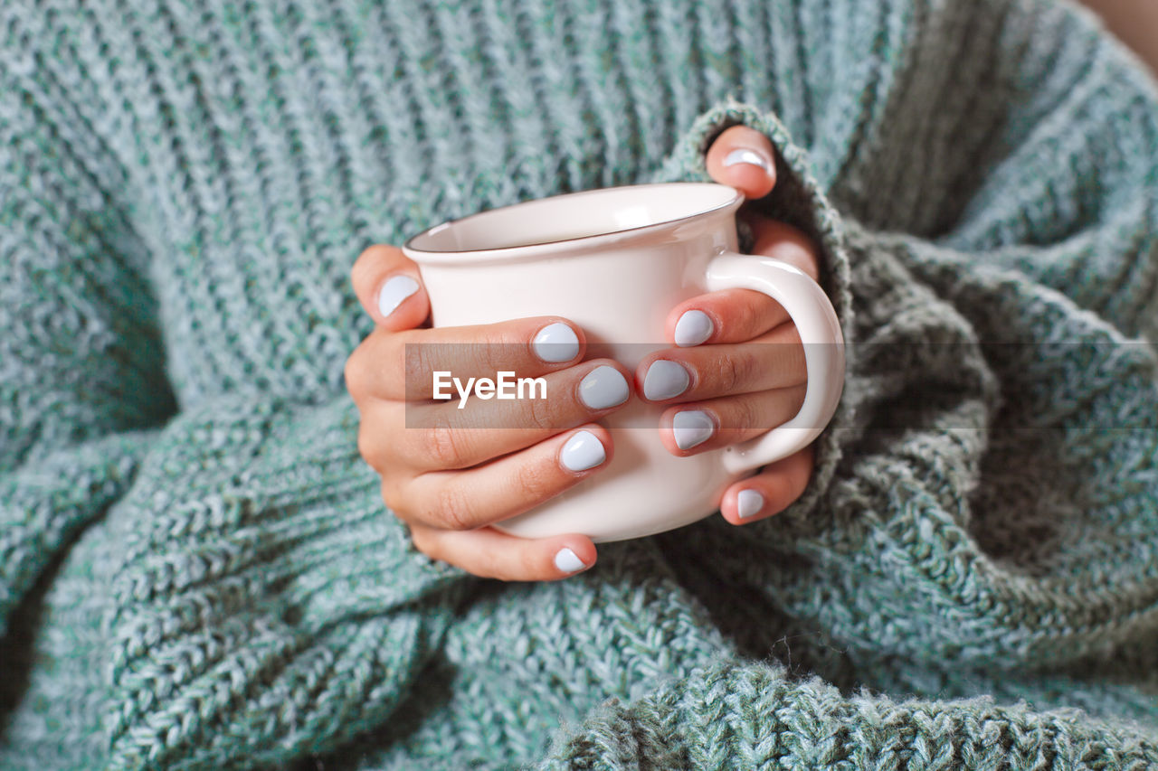 one person, cup, drink, human body part, holding, human hand, hand, mug, close-up, refreshment, warm clothing, sweater, winter, food and drink, clothing, indoors, textile, adult, women, hot drink, tea - hot drink, nail, drinking, scarf, tea cup