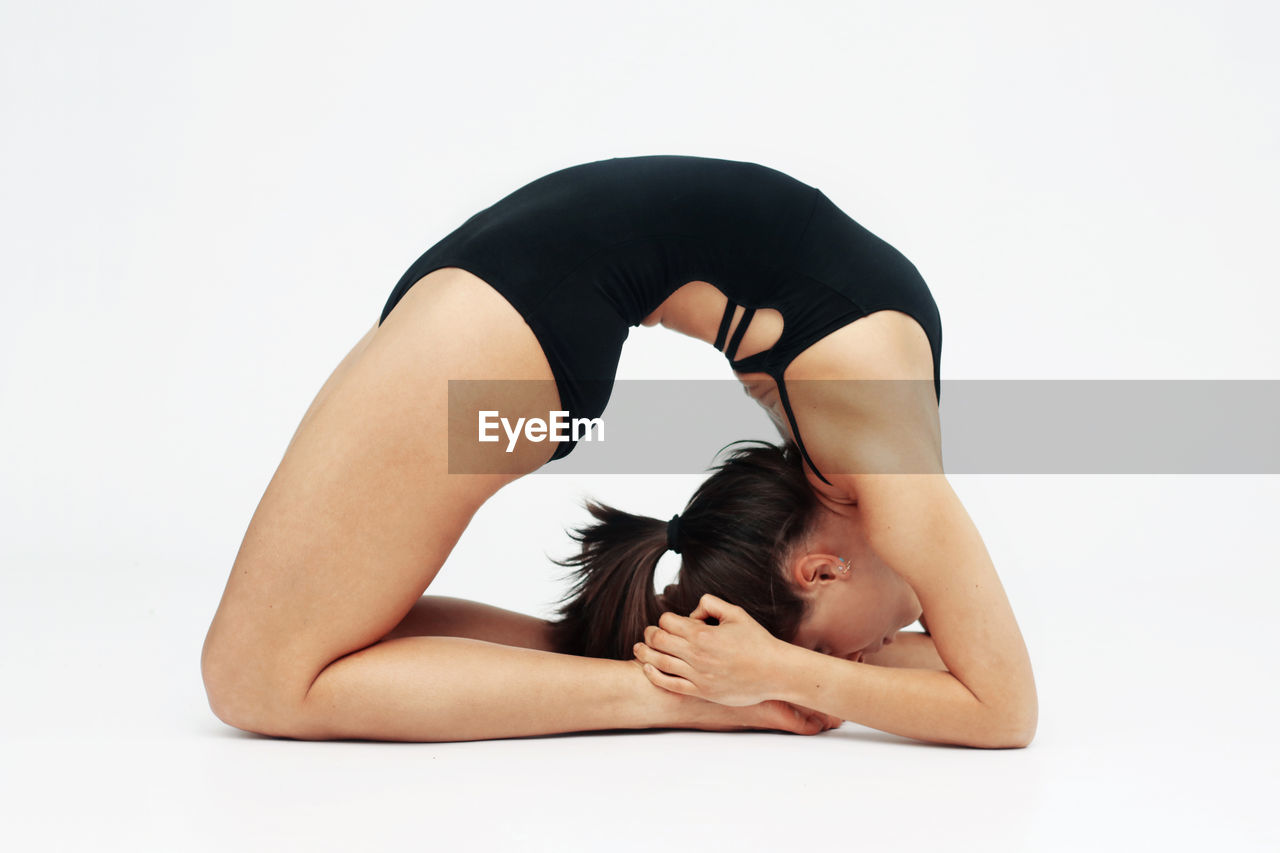 Woman exercising against white background