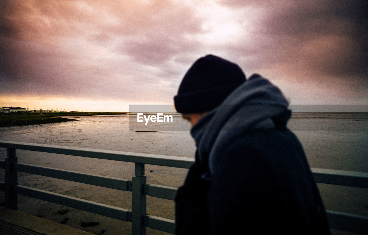 water, sea, real people, one person, nature, sky, sunset, outdoors, boys, standing, leisure activity, childhood, hooded shirt, beauty in nature, lifestyles, horizon over water, scenics, day, warm clothing, close-up, people