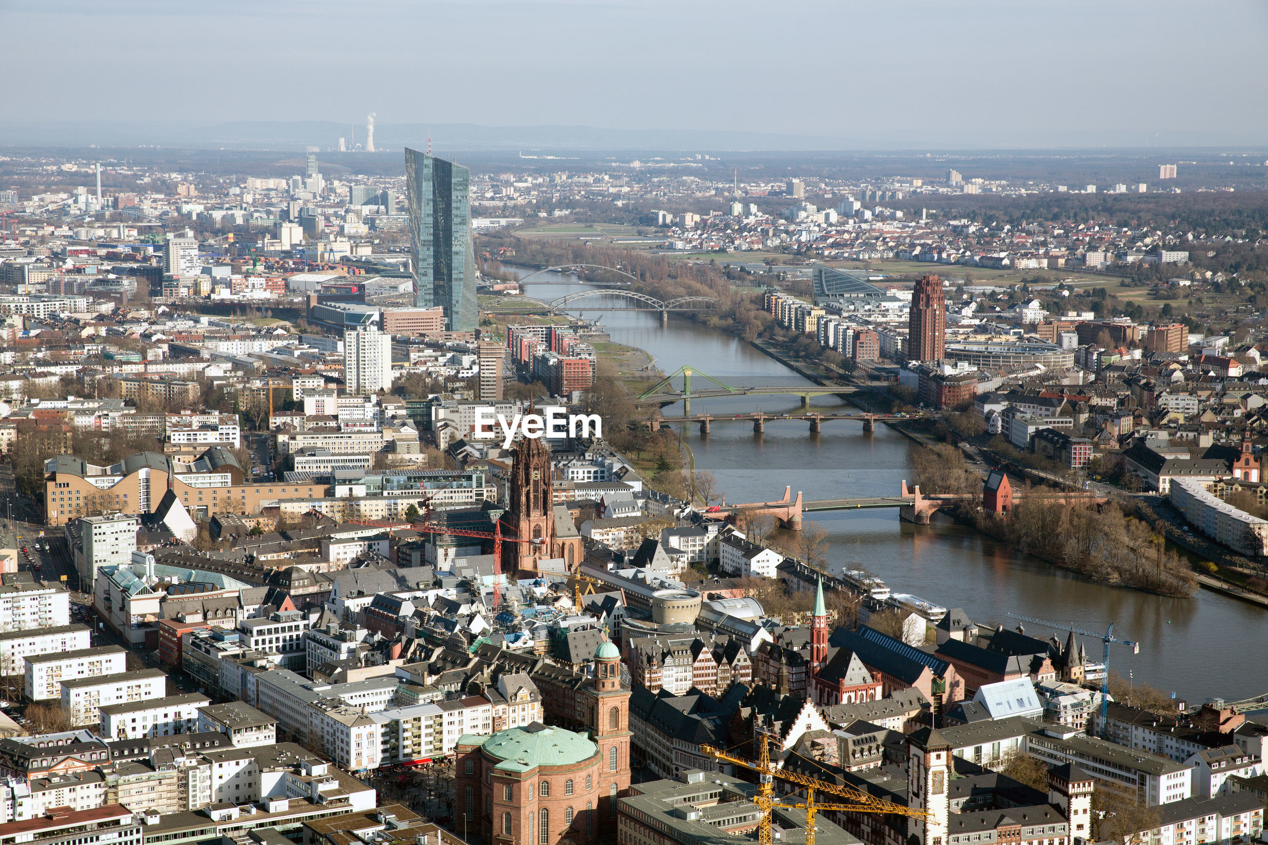 HIGH ANGLE VIEW OF CITY BY RIVER AGAINST SKY