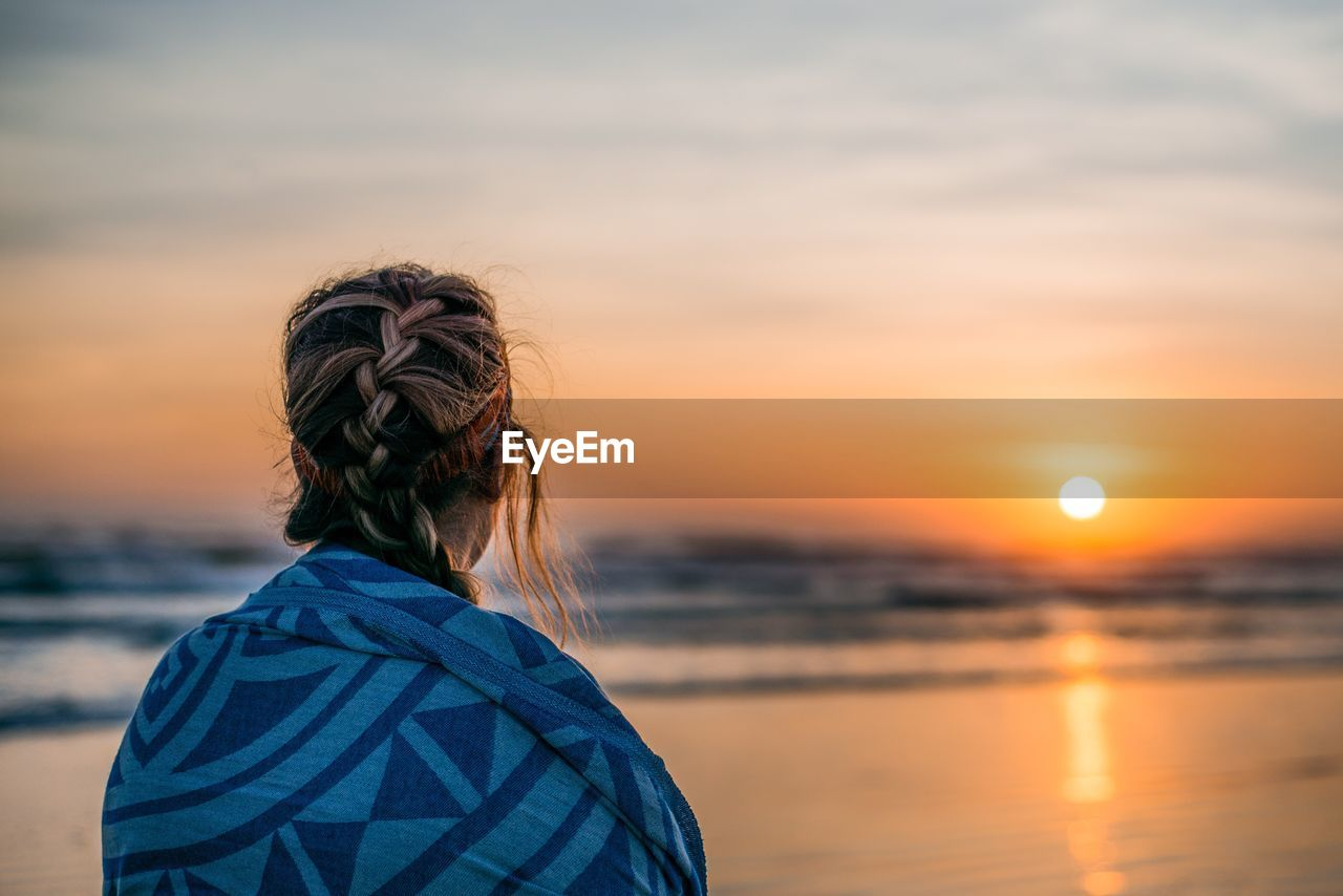 Rear View Of Woman Against Sea During Sunset