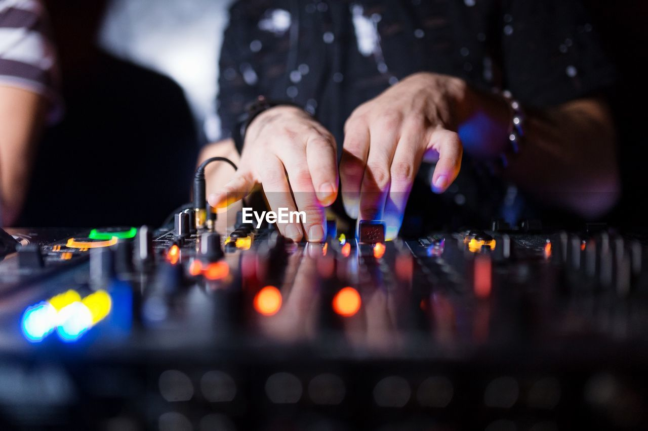 Midsection Of Dj Using Sound Mixer At Night