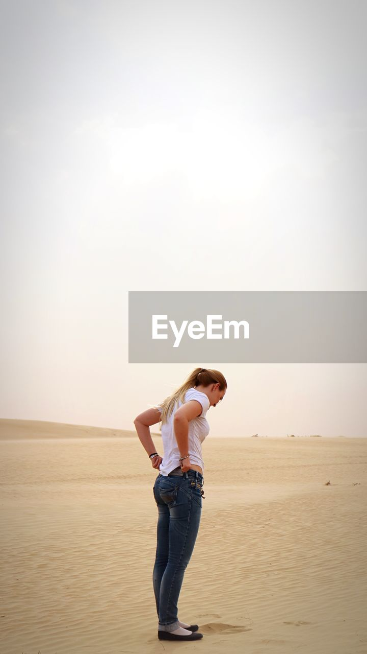 Full Length Of Woman Pulling Jeans While Standing On Sand In Desert
