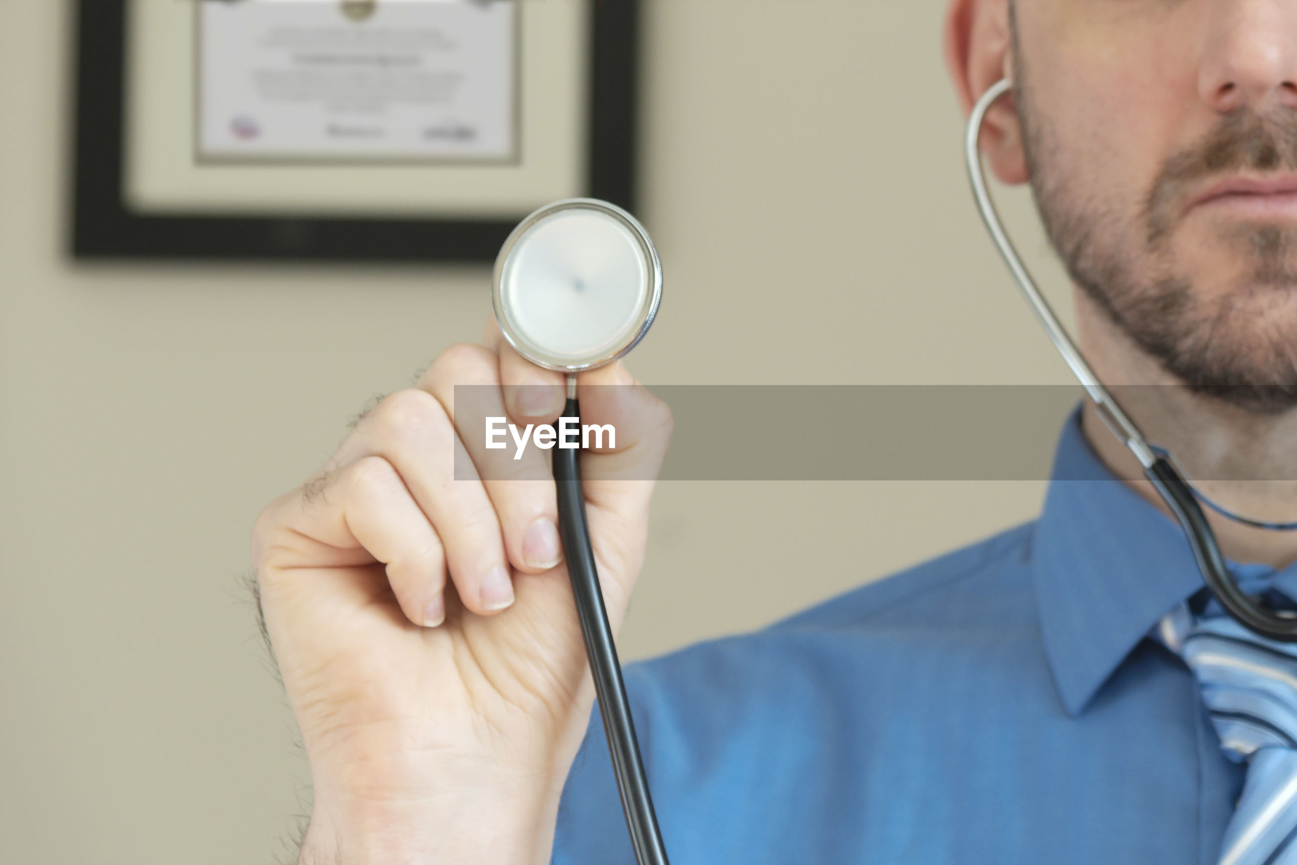 Doctor holding up stethoscope while on video chat diagnosis.
