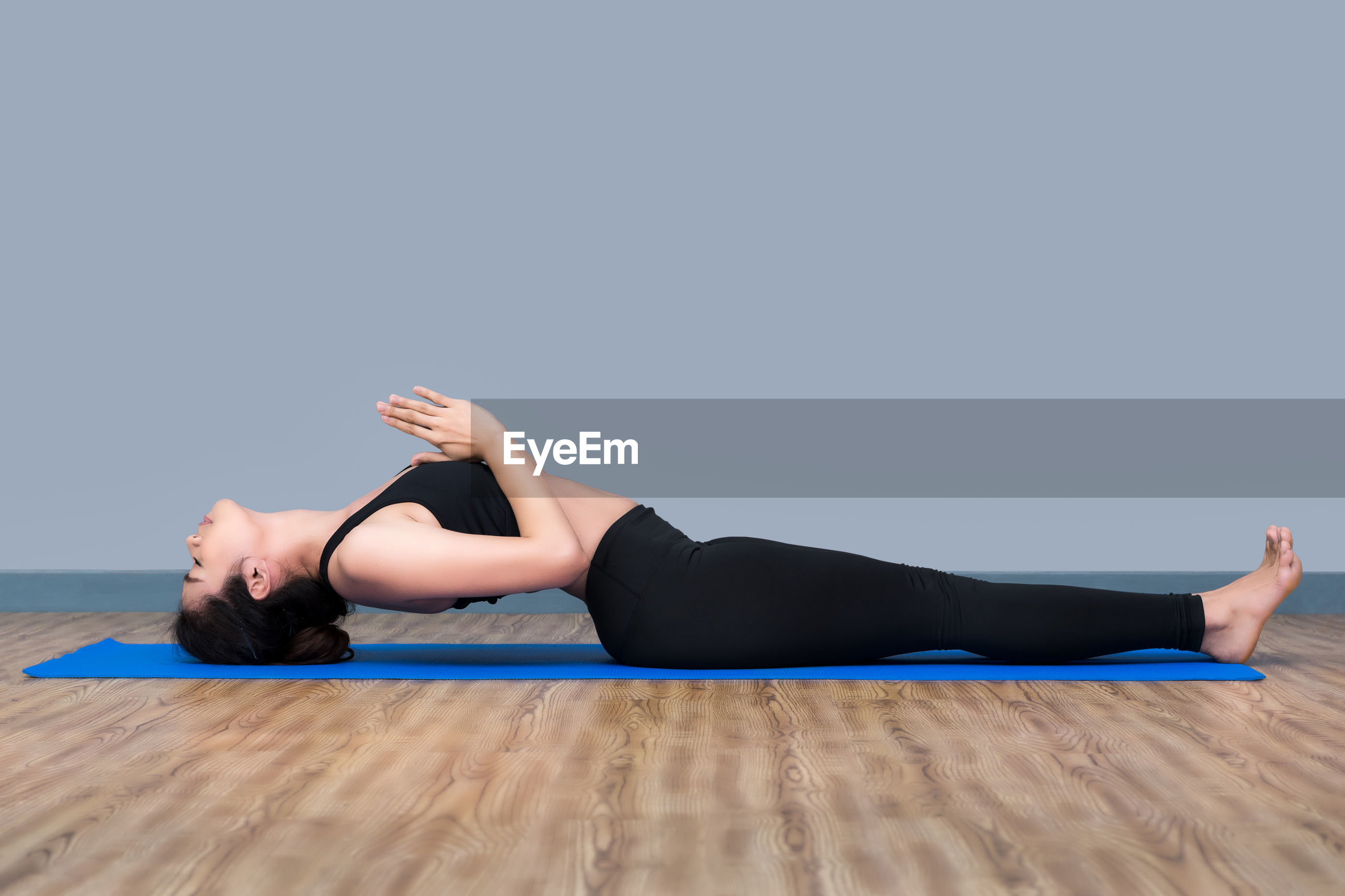 Full length of young woman doing yoga on exercise mat at gym