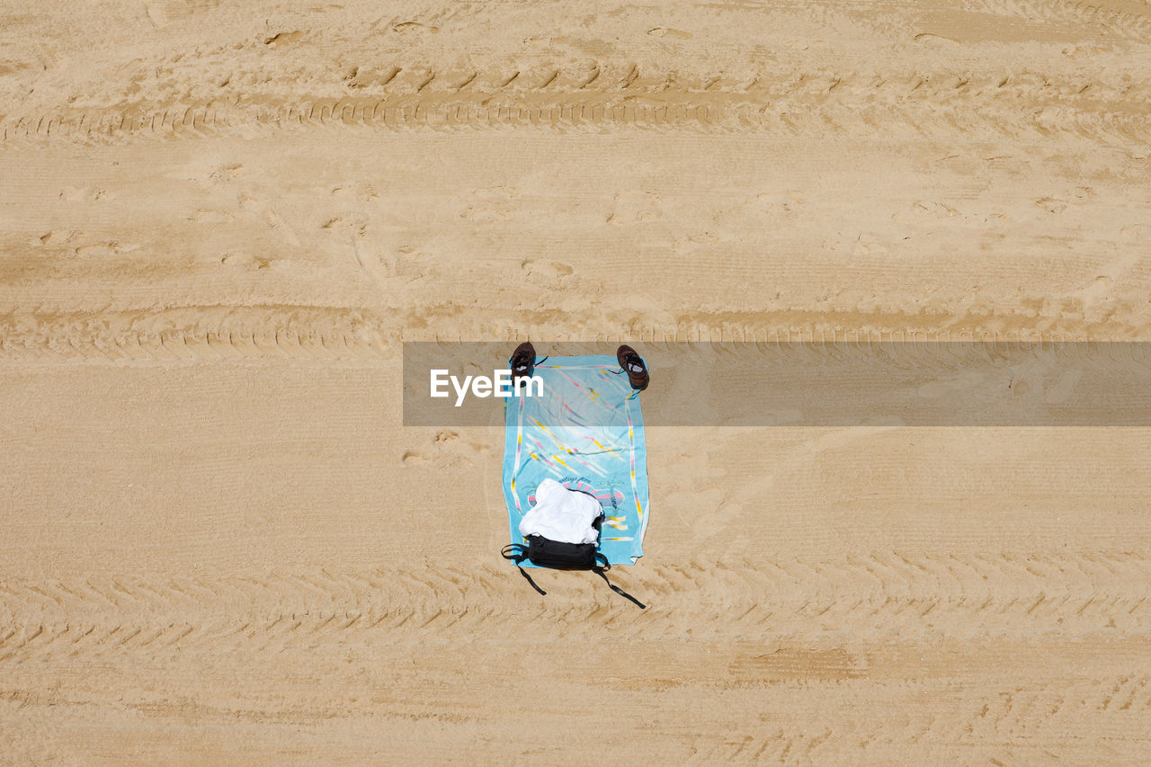 Directly above shot of shoes and towel on sand at beach
