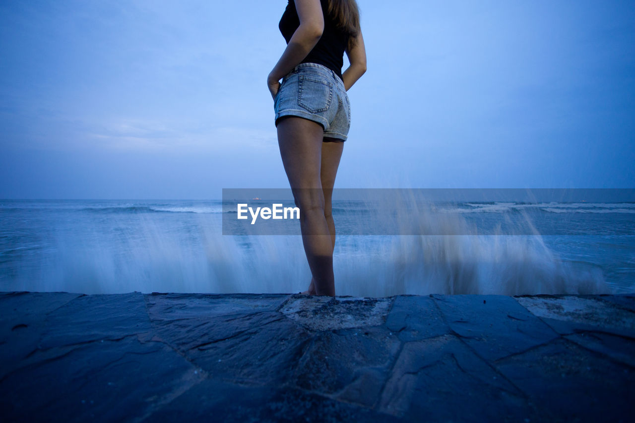 Low Section Of Woman Standing On Rock Formation Against Sky At Dusk