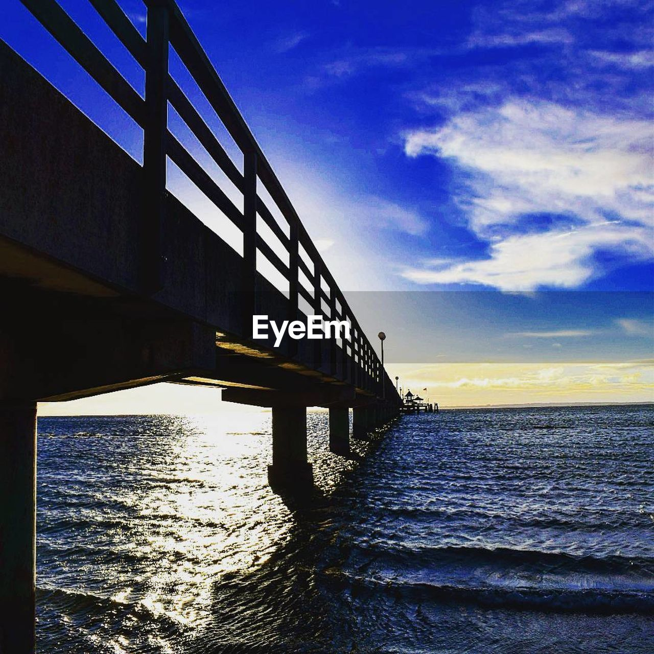 bridge - man made structure, connection, water, built structure, sea, sky, cloud - sky, architecture, sunset, transportation, outdoors, sunlight, no people, horizon over water, nature, blue, day, bridge, low angle view, beauty in nature, scenics