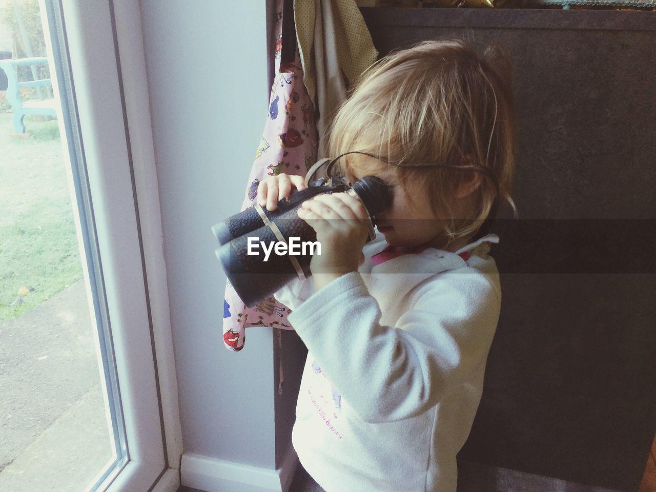 A toddler looking through binoculars