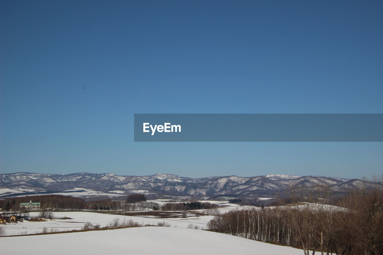 SNOW COVERED MOUNTAINS AGAINST CLEAR SKY