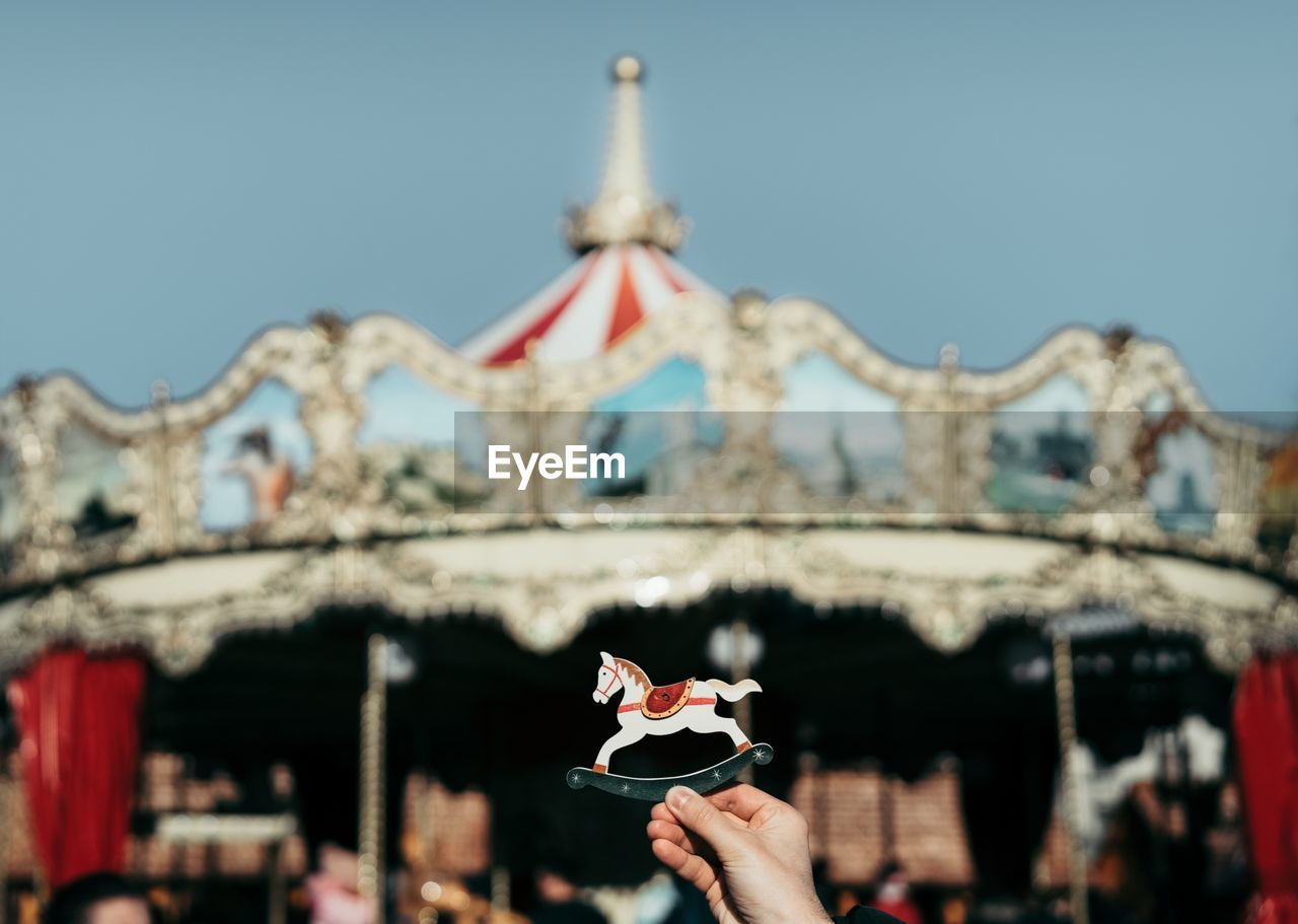 Close-Up Of Hand Holding Toy Against Carousel