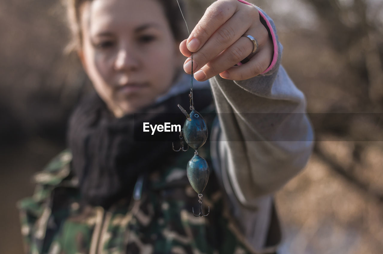 Close-Up Of Woman Holding Blue Fishing Bait