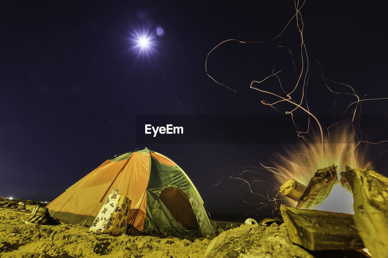 Tent And Campfire On Field Against Sky At Night