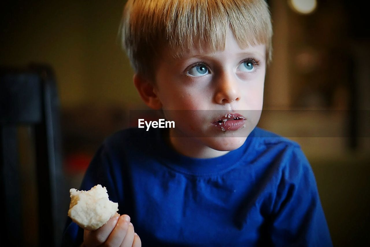 Thoughtful boy eating bread at home