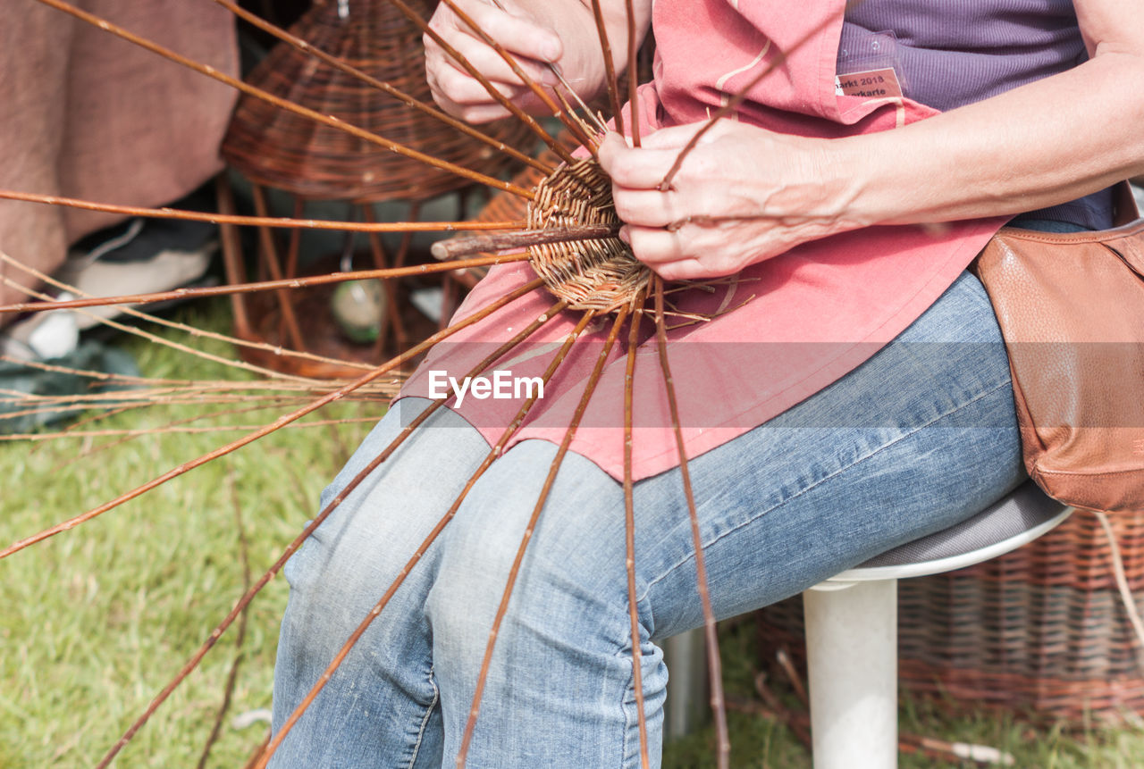 Midsection of woman making wicker basket