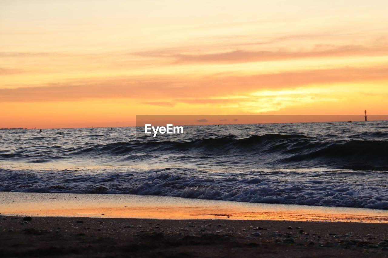sunset, sky, sea, water, beauty in nature, wave, beach, scenics - nature, motion, land, orange color, horizon over water, horizon, cloud - sky, nature, no people, sport, idyllic, aquatic sport, outdoors