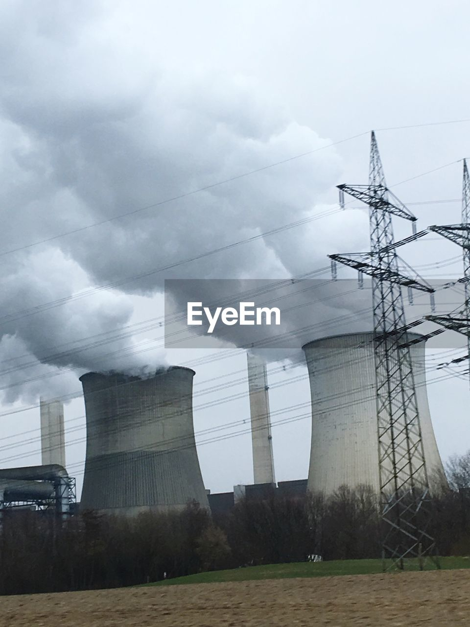 Electricity pylon and nuclear reactor against sky