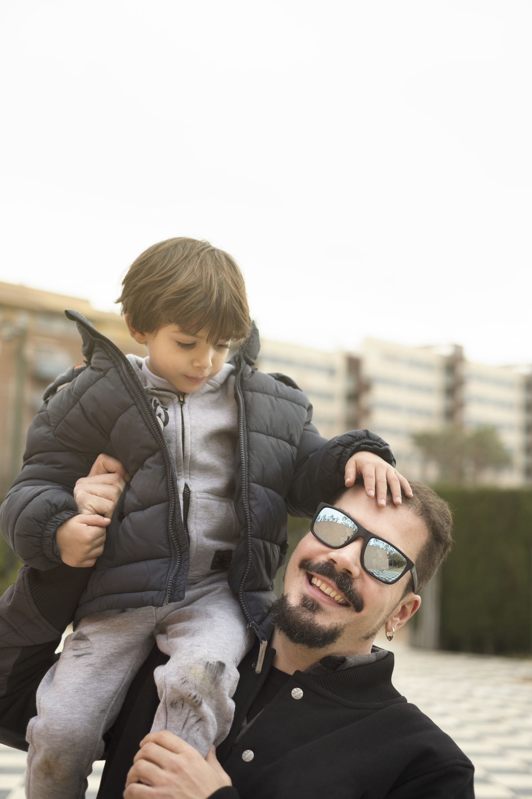 Portrait of happy father carrying son on shoulder while standing outdoors