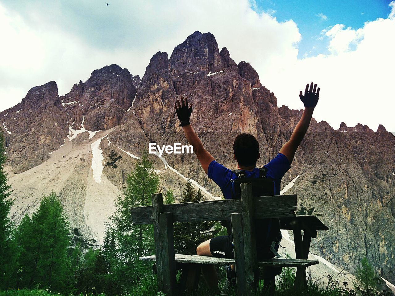 mountain, real people, leisure activity, beauty in nature, one person, sky, lifestyles, scenics - nature, sitting, rock, men, nature, mountain range, solid, rock - object, casual clothing, full length, vacations, day, formation, outdoors, human arm, looking at view