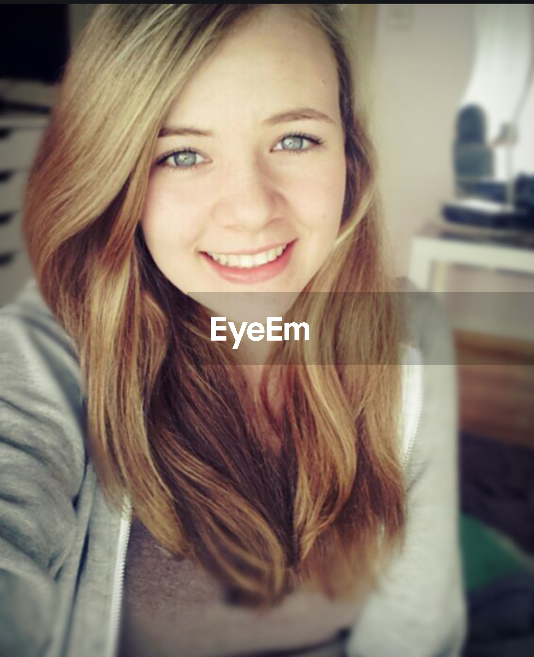indoors, young women, person, young adult, long hair, portrait, headshot, looking at camera, lifestyles, front view, leisure activity, home interior, casual clothing, focus on foreground, close-up, smiling, head and shoulders