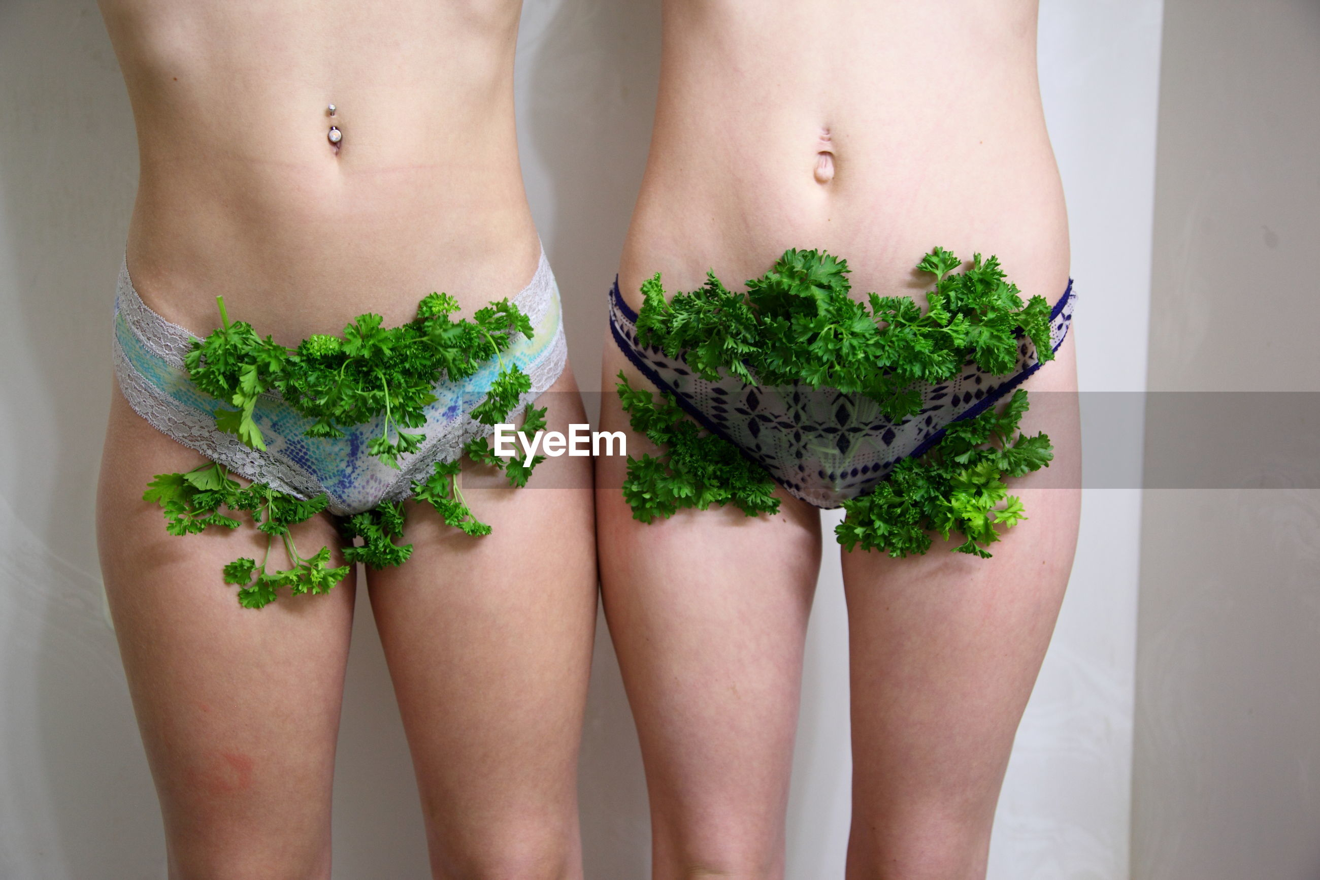 Midsection of female friends with cilantro in panty standing against wall