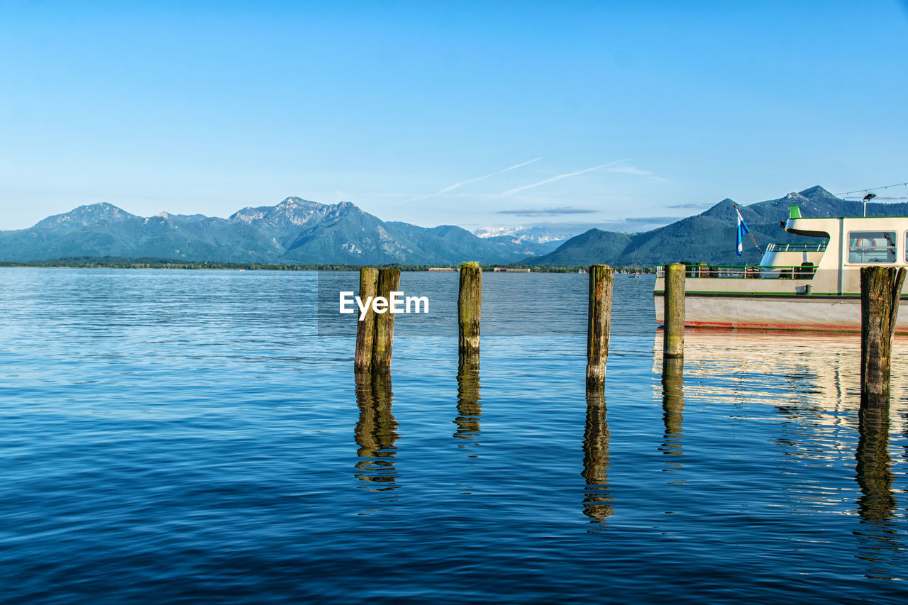 water, mountain, sky, waterfront, beauty in nature, lake, tranquility, blue, no people, tranquil scene, nature, scenics - nature, wood - material, architecture, day, mountain range, built structure, rippled, outdoors, post, wooden post