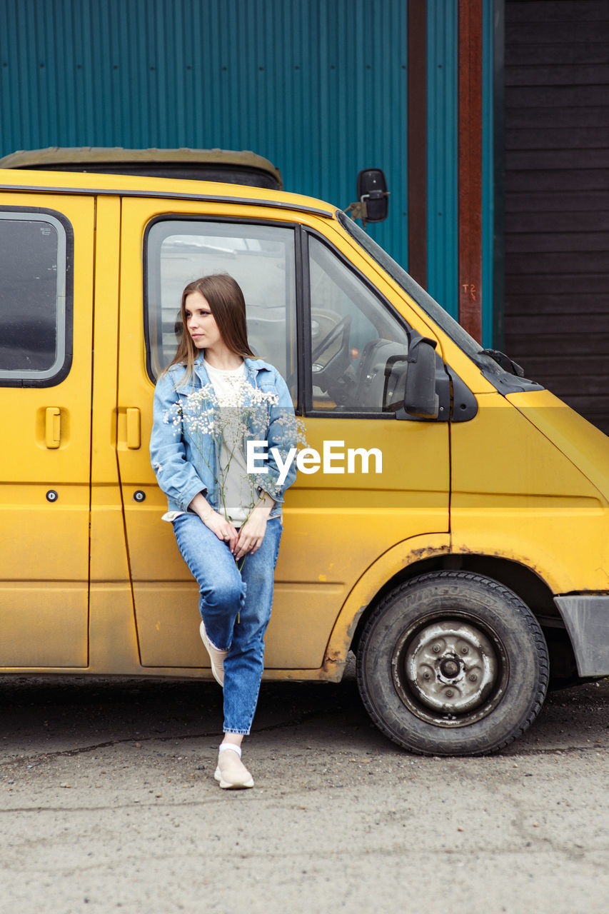 Woman  in jeans near a yellow car, van. full-length portrait of one person. holds in hands flower
