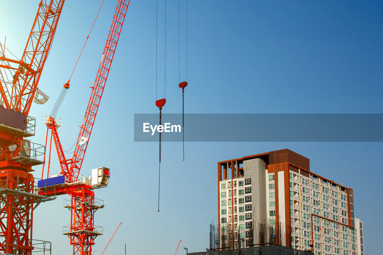 LOW ANGLE VIEW OF CRANES AGAINST BUILDINGS