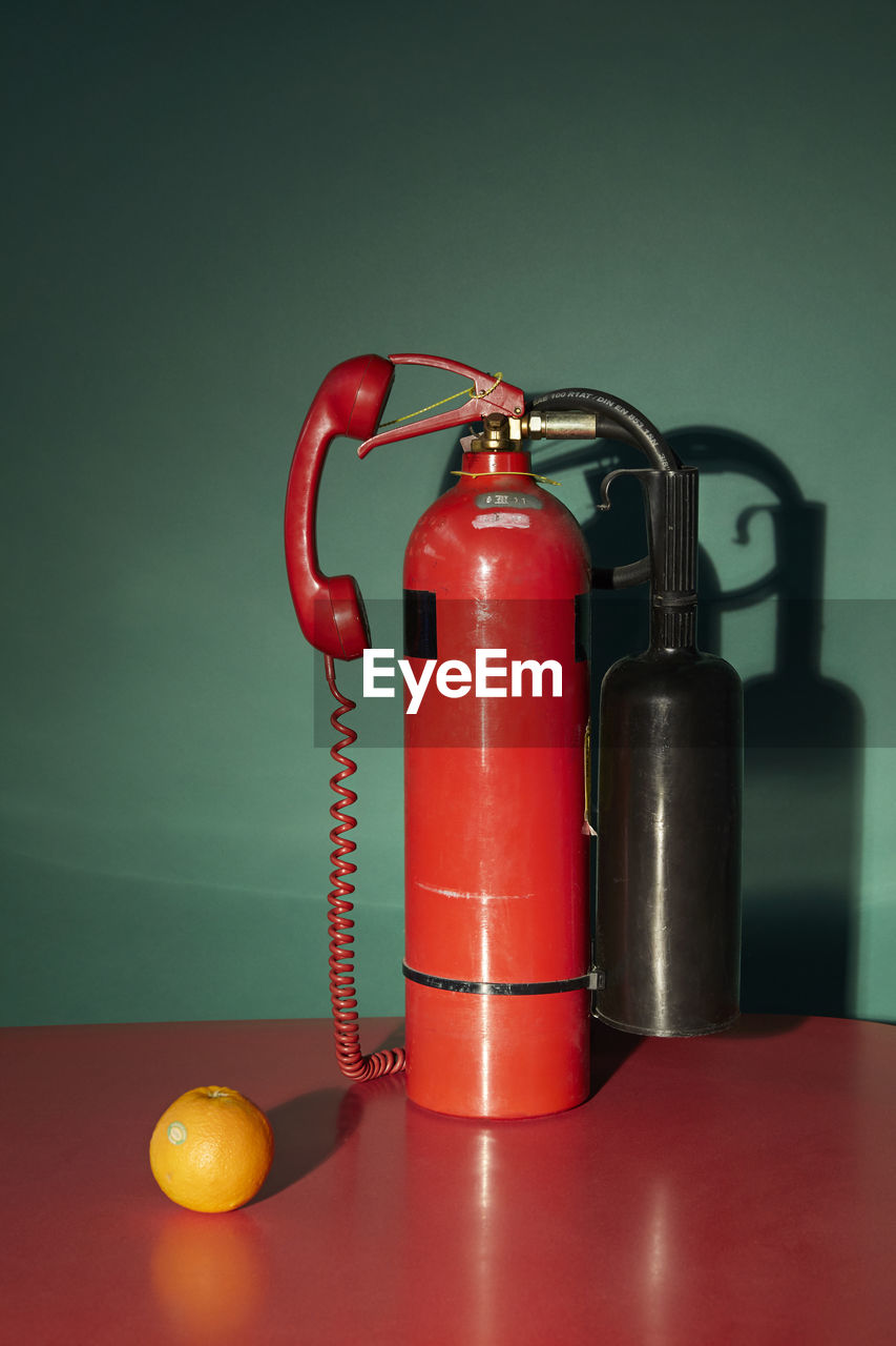 Close-Up Of Fire Extinguisher On Table Against Wall