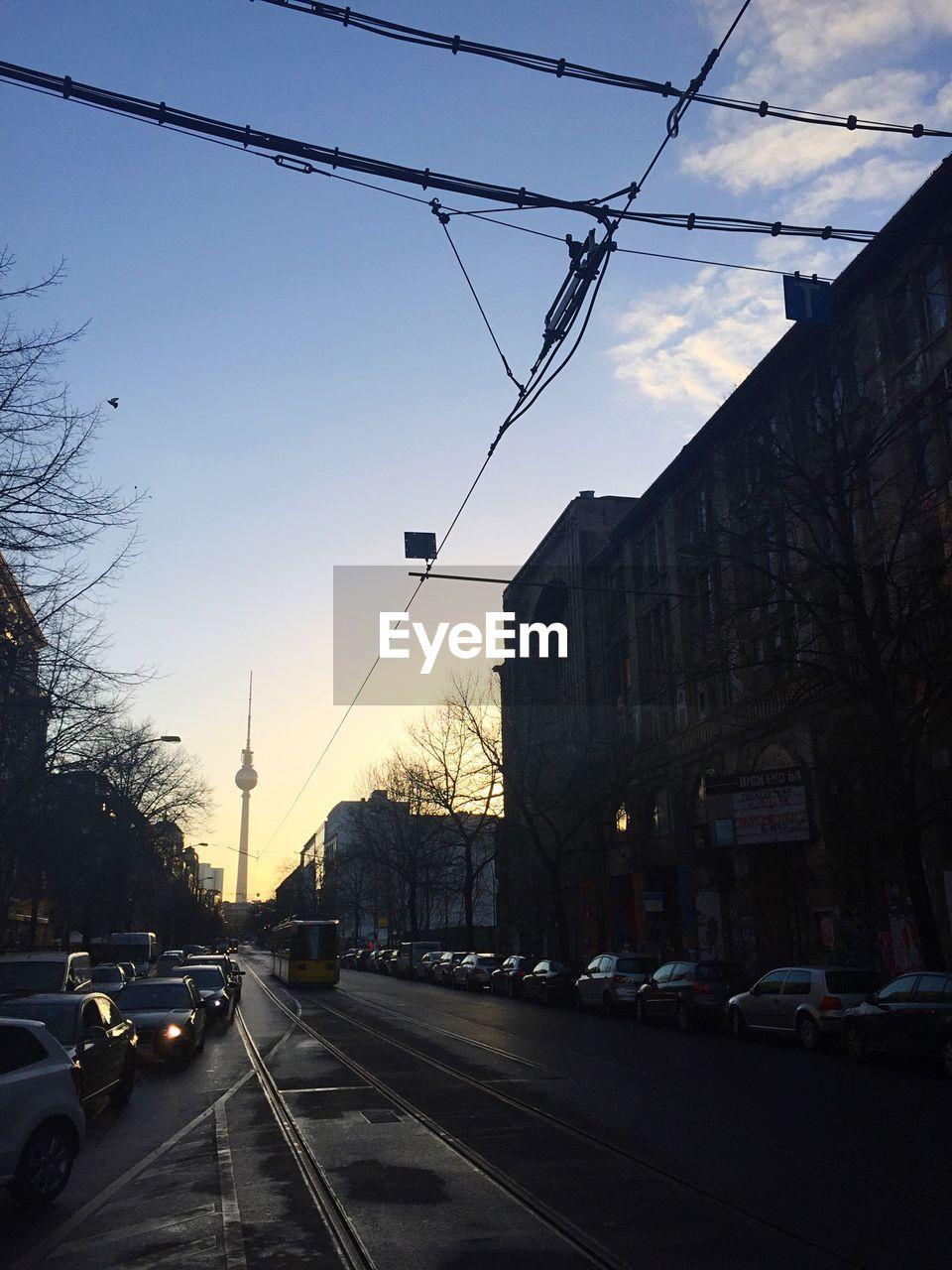 City street leading towards fernsehturm against sky
