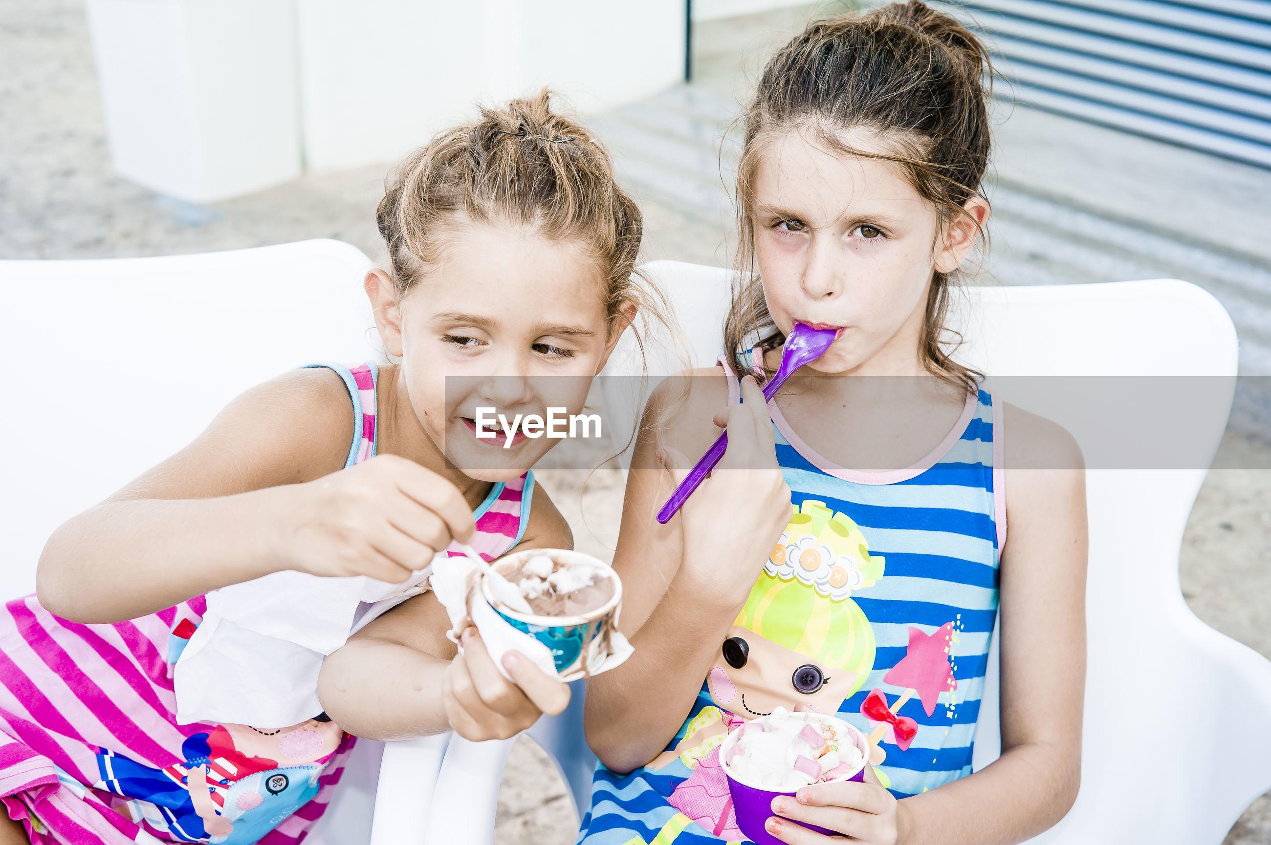 Cute siblings eating ice cream at home