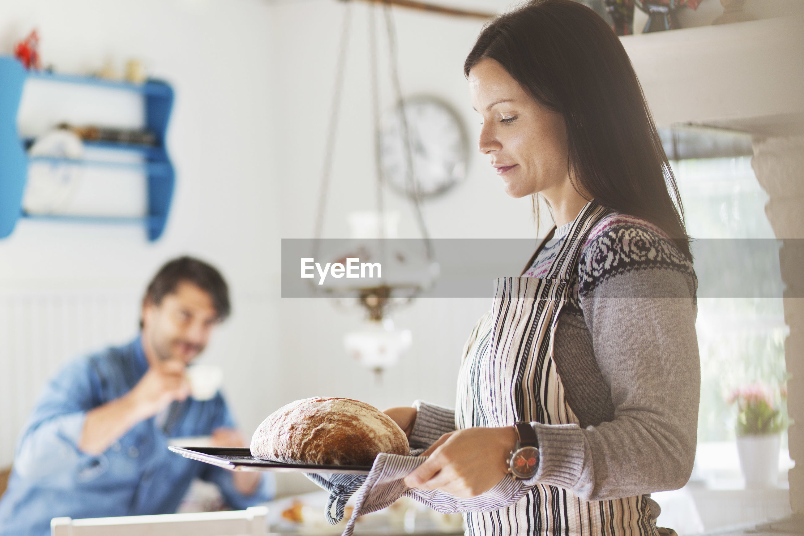 WOMAN HOLDING FOOD IN KITCHEN