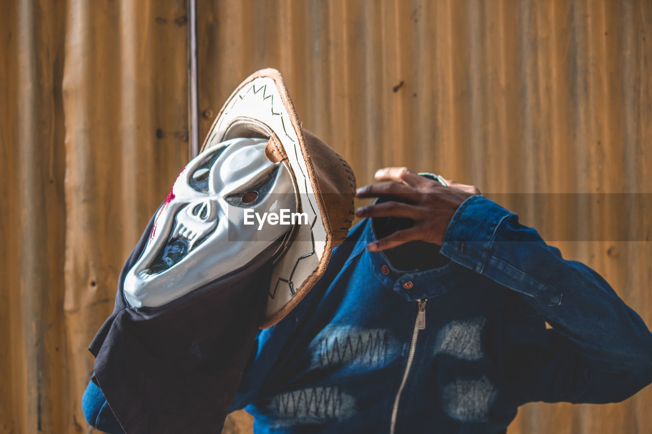 real people, one person, day, leisure activity, focus on foreground, hand, human hand, lifestyles, wood - material, human body part, holding, outdoors, unrecognizable person, casual clothing, clothing, close-up, brown, mask, disguise
