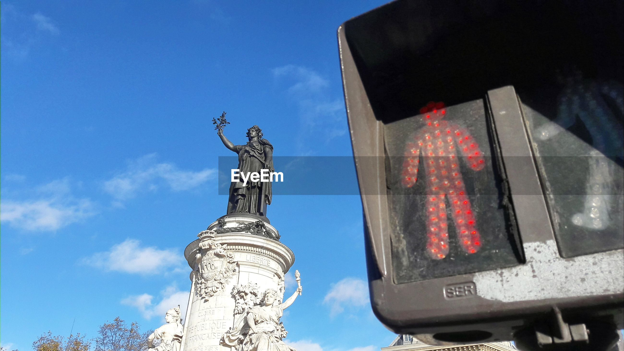 Low angle view of stoplight with statue in background against blue sky